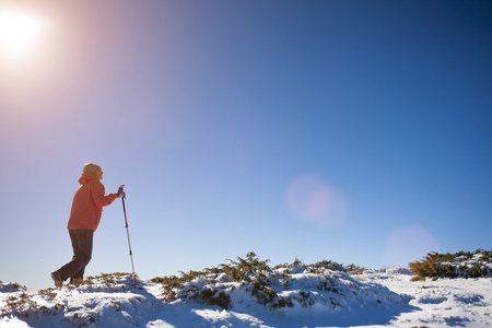 textual: The girl walks in the mountains on snow. Stock Photo