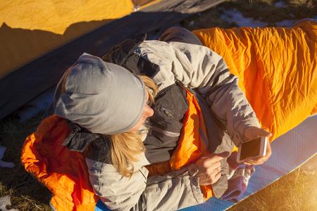 Das Mädchen mit dem Telefon liegen in einem Schlafsack auf die Natur. Standard-Bild - 47814316
