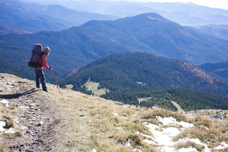 scarring: Tourist with backpack standing on a mountain.