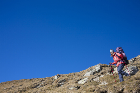 scarring: The girl descends from the high mountains on the background of blue sky. Stock Photo