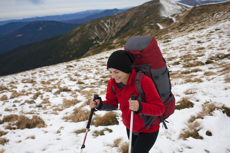 scarring: Girl with a backpack climbs to the top of a high mountain. Stock Photo