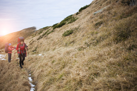 scarring: Two girls with backpacks walk along a trail in the mountains.