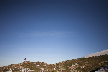 scarring: Silhouette of woman running along a mountain ridge high in the mountains. Stock Photo