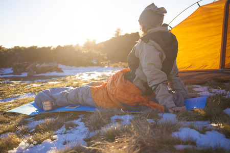 cold beverage: Girl sitting in a sleeping bag with a phone and a drink.
