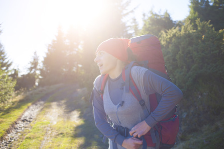 textual: A young girl wearing a large backpack for Hiking in the mountains. Stock Photo