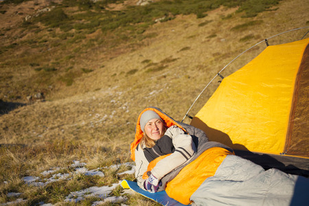 girl in nature: Girl in a sleeping bag lying near the tent.