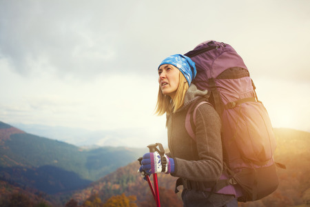 people travelling: Portrait of a beautiful young girl with a backpack in the mountains. Stock Photo