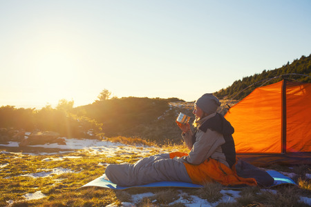Girl in a sleeping bag sitting near the tent and was holding the Cup. Imagens