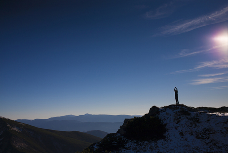 textual: The silhouette of a man in the mountains against the blue sky.