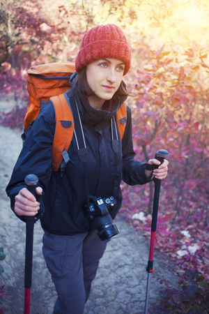textual: The girl with the camera and the backpack goes on the trail in a beautiful forest.