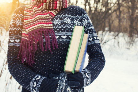 Girl in a wool sweater keeps old books. Imagens - 50629836
