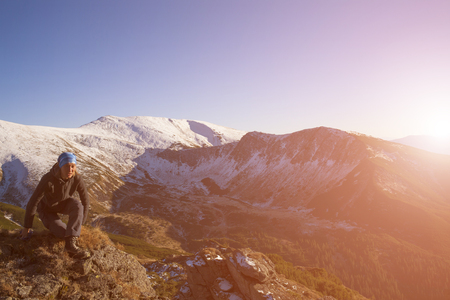scarring: The girl sits on stone and looks at mountains.