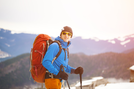 winter sports: A traveler with a backpack and walking sticks.