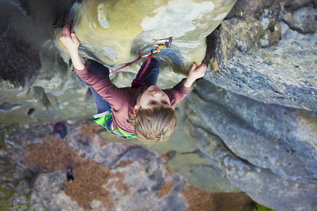 Bold kid rock climber climbs on a difficult wall. Archivio Fotografico