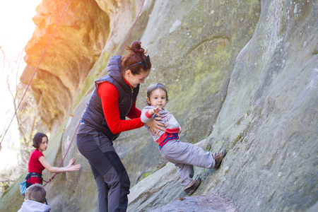 child sport: A little boy tries climbing with mom on the rocks.