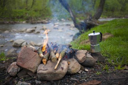 Un fuego y hacer café en un claro cerca del río. Foto de archivo - 57904320