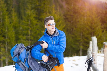 snow climbing: The climber wears a backpack before climbing into the mountains in the snow.