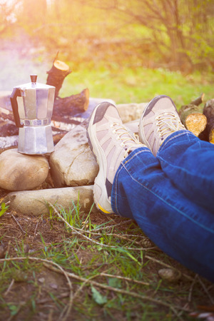awaking: People sitting around a fire at dawn and waiting until the coffee is ready. Stock Photo