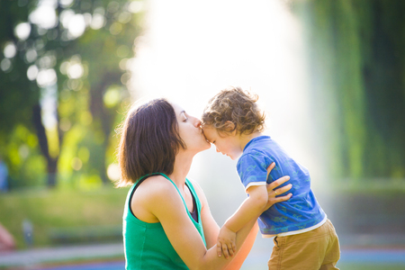 playful behaviour: Young mother kissing her son on the nature. Stock Photo