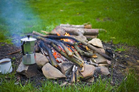 The maker stands near the fire in camping on the nature.
