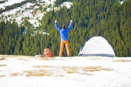 ascent: Climber jumps near the tent after a successful ascent. Stock Photo