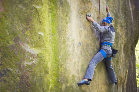 difficult: Girl rock climber climbs difficult route on the cliffs.