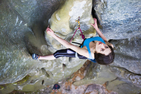 lead rope: Girl rock climber climbs difficult route on the cliffs.
