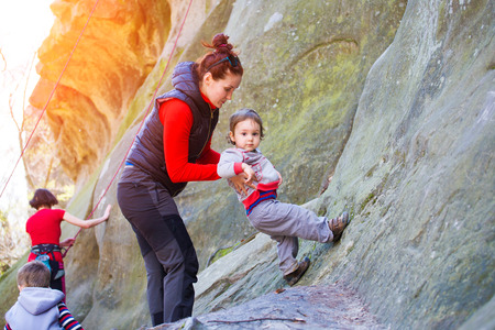 A little boy tries climbing with mom on the rocks.