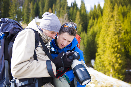 winter photos: The photographer shows the photos to a friend after traveling through the winter mountains.