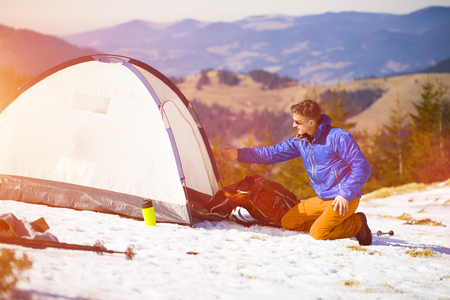 textual: Climber with a backpack near the tent and preparing for the ascent. Stock Photo