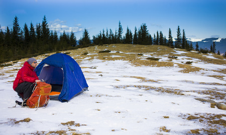 Climber with a backpack near the tent and preparing for the ascent. Stock Photo