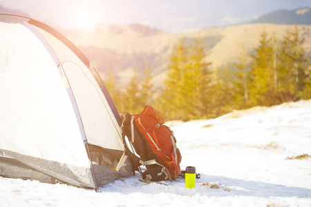 Backpack and belongings for the journey stand near tents in the winter. Stock Photo