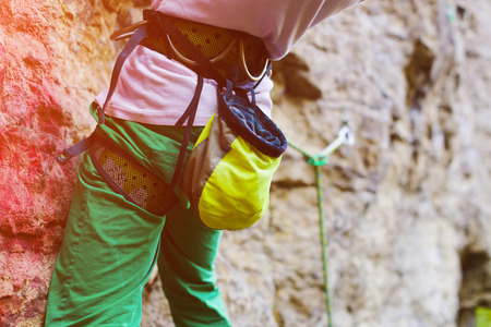 A young woman with a rope engaged in the sports of rock climbing on the rock. Stock Photo