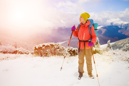 snow climbing: girl with backpack walking on snow in the mountains and mountain climbing during the winter holidays.