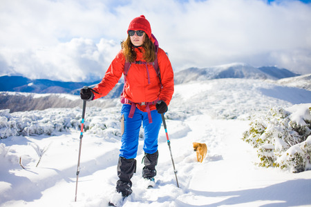 girl with dog walking on the trail in the mountains, winter in the mountains. Stock Photo