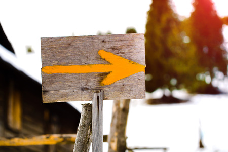 wooden pointer to the route in the mountains, the arrow on the sign.