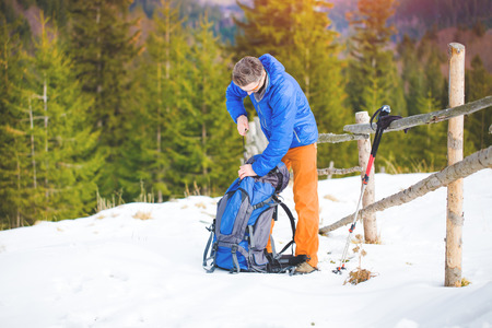 climber looking for things in a backpack during a winter hike in the mountains.