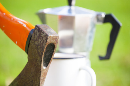 axe with the red handle on the background of geyser coffee makers and white mug.