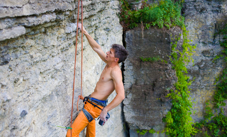 rock climber climbs the cliff using ropes and equipment, the employment of sports climbing.
