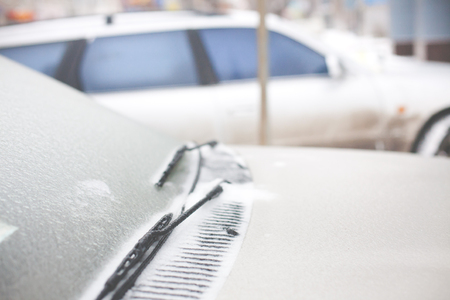 icy conditions: icy windshield and the wipers at the gray car in the winter. Stock Photo