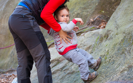 the little boy is trying to climb on the rock, and mother helps him. Stock Photo