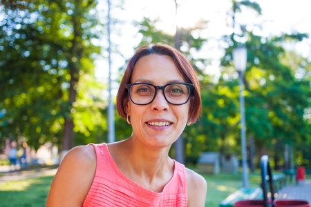 Portrait of young beautiful women exists in glasses on a background of green trees, brunette with short hair relaxing in the park.