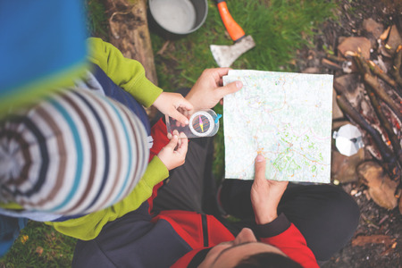 The boy with his father sitting near the fire and keep a compass and a map, dad teaches son how to use a map and compass, man and child made a camping and sitting by the fire.