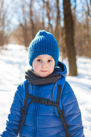 Portrait of little boy in the blue knit cap in winter, child standing on the trail in the winter woods, a boy with a backpack standing in the snow.