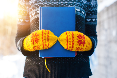 The girl in the knitted sweater and mittens holds two books against the winter snow.