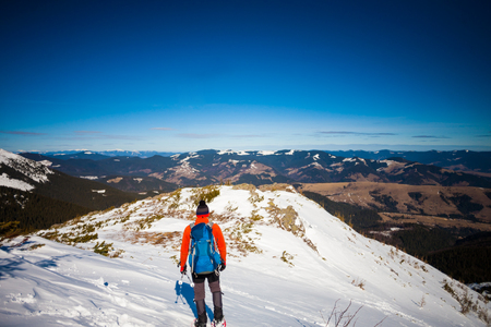 Man in snowshoes with trekking poles goes up in the mountains in winter, the climber with a backpack walking on snow on a Sunny day on the background of blue sky.