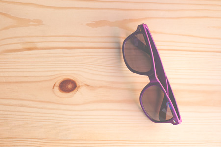 Purple sunglasses lying on a wooden table.