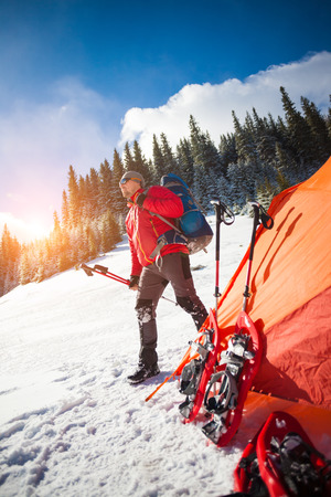 The man with the blue backpack is standing near the orange tent, trekking poles and snowshoes are on the snow near the tent.