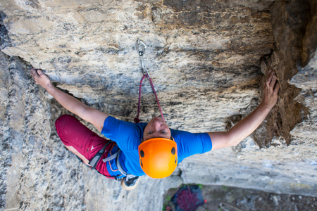 thrilling: Climber in a helmet climbs to the top of the mountain. Sport activities in nature.