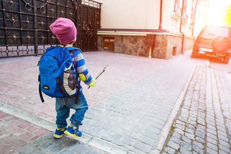 A boy with a backpack walking across the street. A small child in a striped sweater goes through the city.